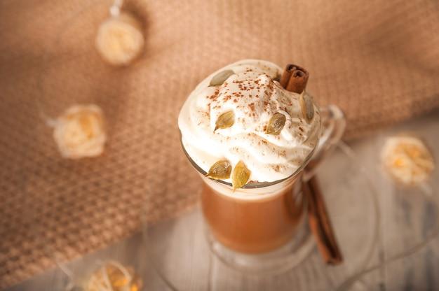 Dynia latte w przezroczystym kubku zbliżenie i skopiuj miejsce latte z kremem cynamonowe pestki dyni na białym talerzu latte i sweter