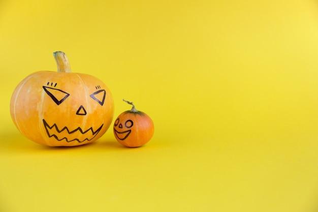 Dynia matka i dziecko z przerażającym uśmiechem złe twarze na żółtym tle koncepcji szablonu haloween