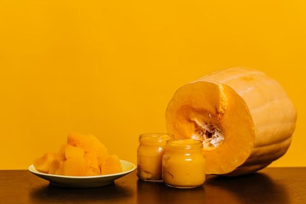 Dynia na stole, słoiki z dyniowym puree i dynia pokrojona na talerzu, stoją na żółtym tle. koncepcja zdrowej żywności.
