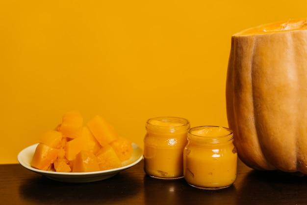 Dynia na stole, słoiki z dyniowym puree i dynia pokrojona na talerzu, stoją na żółtym tle.