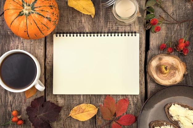 Dynia, notatnik, talerz z kanapkami, aparat fotograficzny, jesienne liście i jagody na naturalnym drewnianym tle.