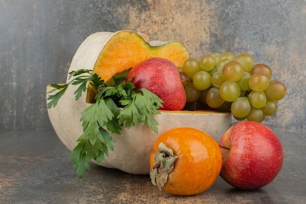 Dynia z jabłkami i winogronami na marmurowej ścianie.