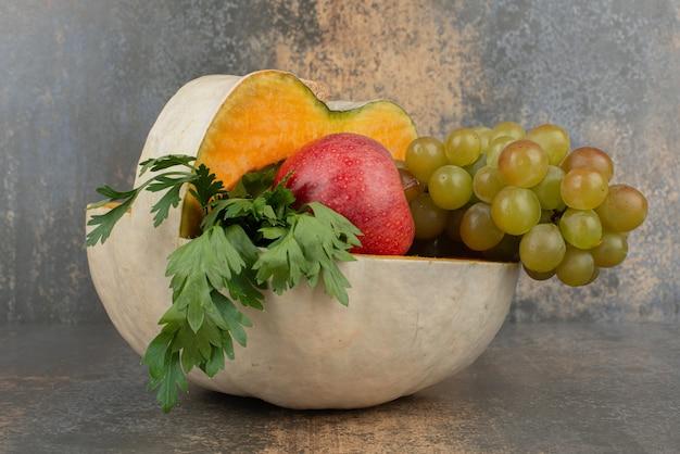 Dynia z jabłkami i winogronami na marmurowym stole.