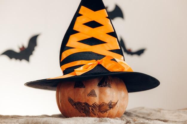 Dynia z pomalowaną twarzą i kapeluszem wiedźmy. koncepcja halloween.