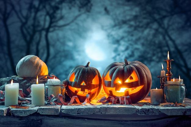 Dynie halloween na ciemnym lesie niebieskim tle