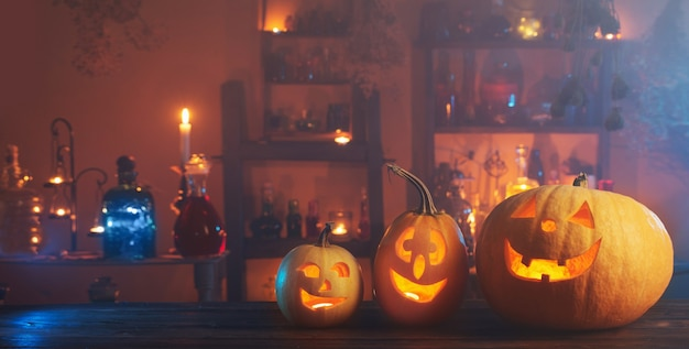 Dynie halloween ze świecami i magicznymi miksturami w nocy w pomieszczeniu