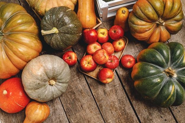 Dynie i czerwone jabłka na podłoże drewniane