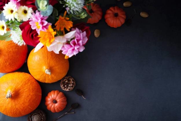 Dynie. jesień kreatywny flatlay, ciemne tło ze świecami, jesienne kwiaty, szyszki i dynie.