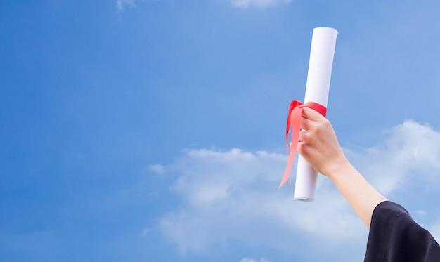 Dyplom z czerwonym faborkiem w ręce na nieba tle