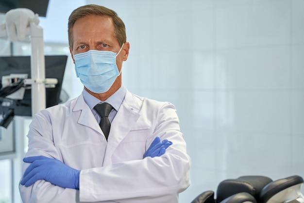 Dyplomowany dentysta w masce stojący ze skrzyżowanymi rękoma