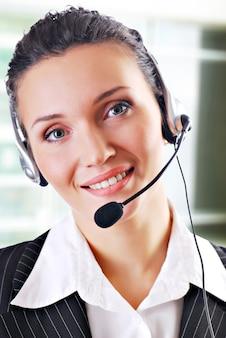 Dyrektor biura pracujący jako personel obsługi klienta, noszący zestaw słuchawkowy z mikrofonem.