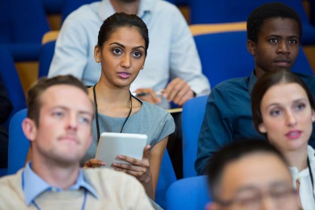 Dyrektor biznesowy uczestniczący w spotkaniu biznesowym, sporządzając notatki w centrum konferencyjnym