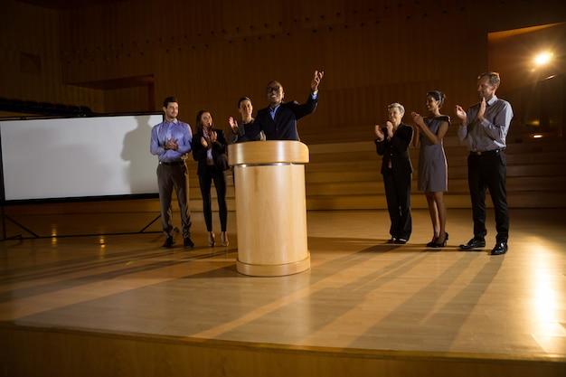 Dyrektor biznesowy wygłasza przemówienie, podczas gdy koledzy biją brawo w centrum konferencyjnym