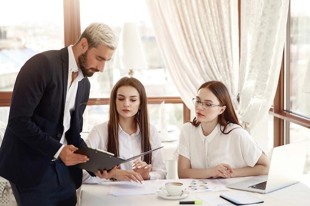 Dyrektor restauracji pokazuje schematy finansowe w dokumentach, a dwie asystentki, kobiety, słuchają z uwagą