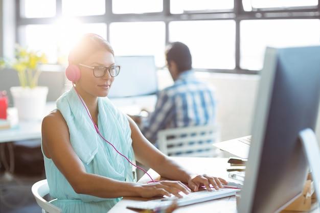 Dyrektor wykonawczy słucha muzyka podczas gdy pracujący na komputerze