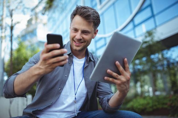 Dyrektor wykonawczy używa telefon komórkowego i cyfrową pastylkę