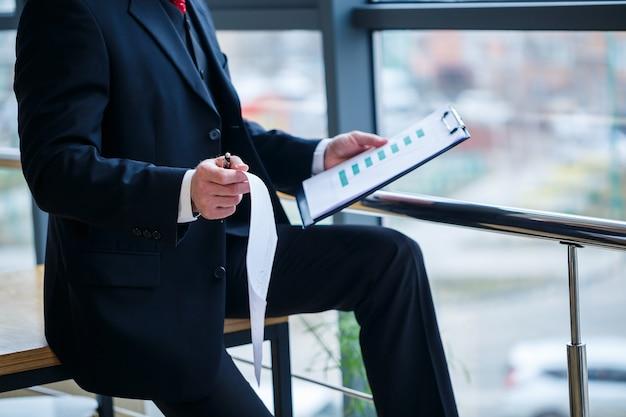 Dyrektor zarządzający mężczyzna oparł się o drewniany stół w swoim biurze przy dużym oknie i przygląda się udanemu planowi rozwoju firmy.