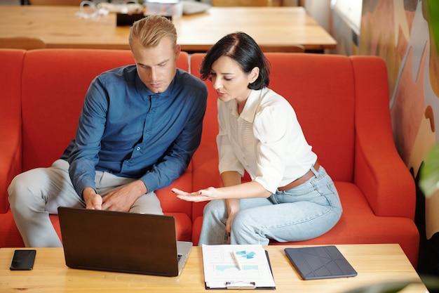 Dyrektorzy biznesowi oglądający prezentację produktu na ekranie laptopa i omawiający szczegóły