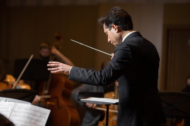 Dyrygent orkiestry symfonicznej z wykonawcami na tle sali koncertowej