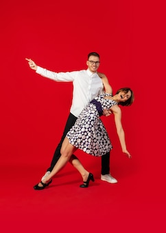 Dyskoteka. oldschoolowy styl młoda para taniec na białym tle na czerwonym tle studio. moda artystyczna, koncepcja ruchu i działania, kultura młodzieżowa, powrót mody. młody stylowy mężczyzna i kobieta.