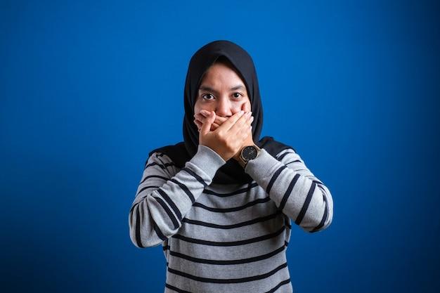 Dyskryminacja kobiet muzułmańskich. islamska dama w hidżabie zamyka usta skrzyżowanymi dłońmi, nie może nic powiedzieć na niebieskim tle, wolna przestrzeń