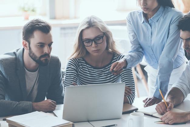 Dyskusja biznesowa. grupa młodych ludzi biznesu siedzących przy biurku i dyskutujących o czymś, patrząc razem na laptopa
