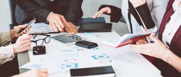 Dyskusja biznesowa na briefingu w biurze. komunikacja w zespole i analiza statystyk danych. dłoń wskazująca na tablet z wykresami
