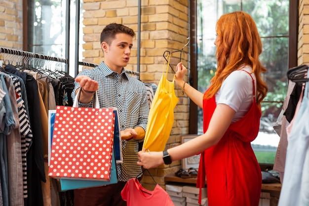 Dyskusja emocjonalna. emocjonalna młoda para rozmawiająca o ubraniach podczas zakupów w popularnym sklepie z modną odzieżą