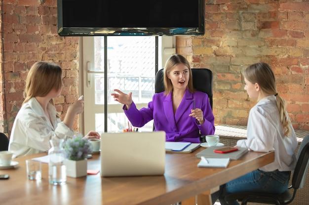 Dyskusja. młoda biznesowa kaukaski kobieta w nowoczesnym biurze z zespołem. spotkanie, dawanie zadań. kobiety pracujące w biurze. pojęcie finansów, biznesu, girl power, integracji, różnorodności, feminizmu.