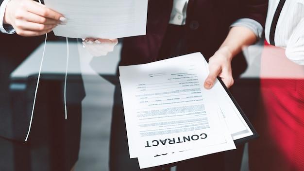 Dyskusja na temat umowy biznesowej. legalne dokumenty korporacyjne. kobieta trzyma w rękach oficjalne dokumenty.