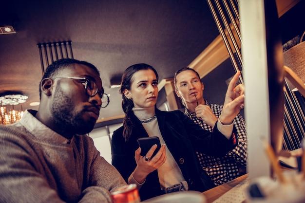 Dyskusja zbiorowa. skoncentrowany mężczyzna stojący w tle i słuchający swoich partnerów