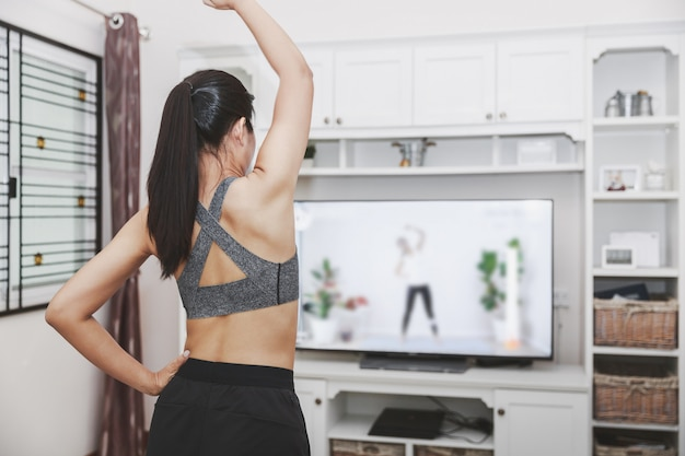 Dysponowana azjatykcia kobieta trenuje sprawności fizycznej ćwiczenia sporta treningu online klasę na telewizorze z domu
