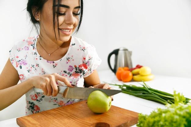 Dysponowana brunetka ciie zielonego jabłka na drewnianej desce w kuchni