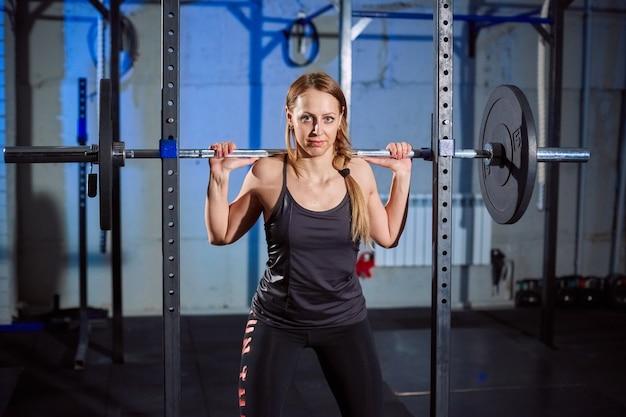 Dysponowana dziewczyna ćwiczy budować mięśnie. fitness i kulturystyka