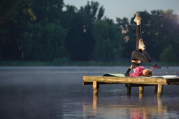 Dysponowana dziewczyna robi ćwiczeniom na rzece