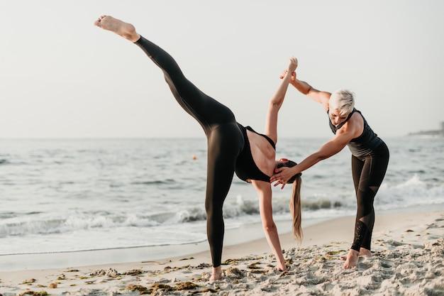 Dysponowana kobieta pomaga sporty dziewczynie ćwiczyć joga asanę na plaży blisko oceanu