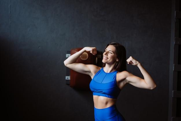 Dysponowana kobieta pozuje na kamerze. osobisty trener pokazujący jej formę. piękno nowoczesnego sportu.