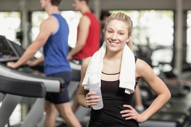 Dysponowana kobieta pozuje z rękami na biodrach przy gym