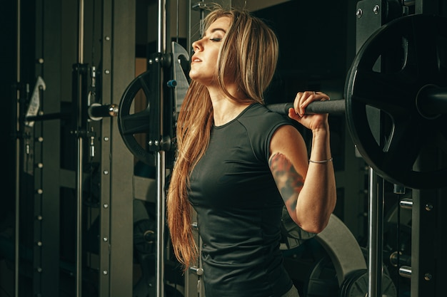 Dysponowana kobieta robi kucnięciom w smith maszynie w gym