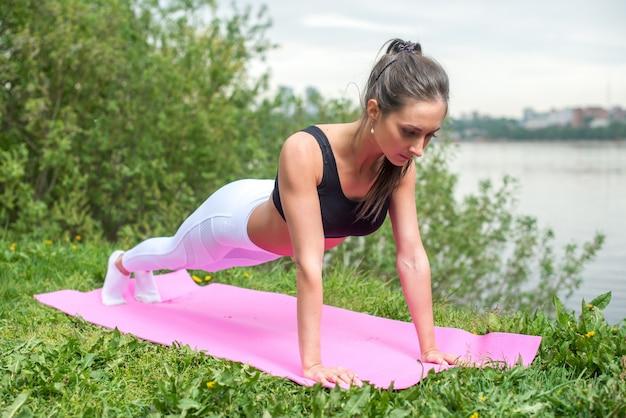 Dysponowana kobieta robi pełnego deski rdzenia ćwiczenia sprawności fizycznej szkoleniu pracującemu na zewnątrz out