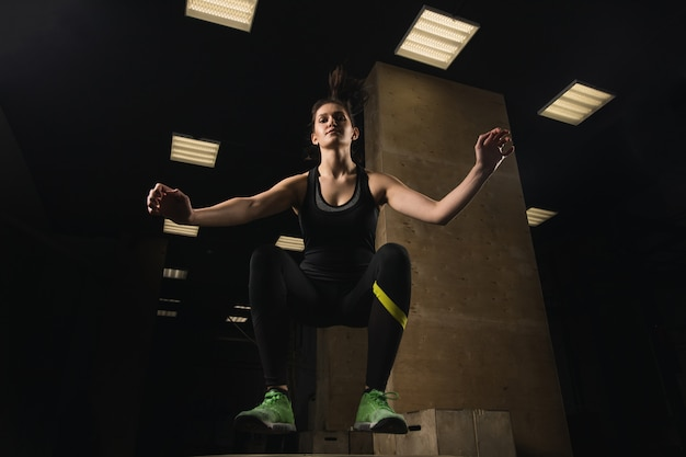 Dysponowana kobieta robi pudełkowatemu doskakiwaniu przy crossfit gym
