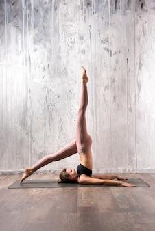 Dysponowana kobieta robi salamba sarvangasana joga pozie