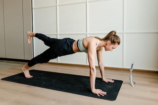 Dysponowana kobieta robi sportowi treningowi w domu z szkoleniem online