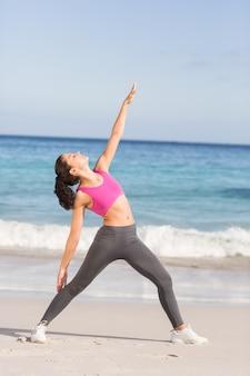Dysponowana kobieta robi sprawności fizycznej obok morza