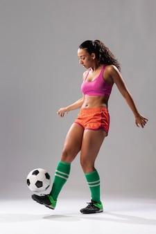 Dysponowana kobieta robi sztuczkom z piłką