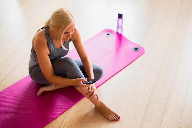 Dysponowana kobieta sprawdza telefon na joga macie