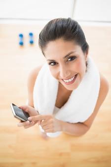 Dysponowana kobieta używa smartphone bierze przerwę od treningu ono uśmiecha się przy kamerą