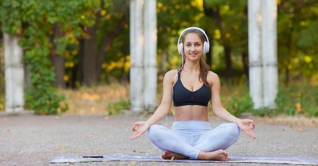 Dysponowana kobieta w sportowym ubraniu siedzi w lotos pozie w parku i słucha muzyki na hełmofonach. zdrowy tryb życia. joga i relaks koncepcja.
