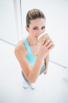 Dysponowana kobieta w sportswear pije kawę
