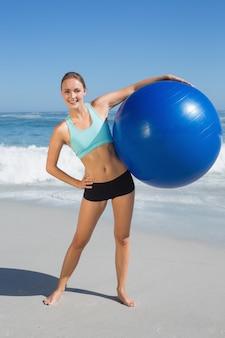 Dysponowana kobiety pozycja na plażowej mienia ćwiczenia piłce